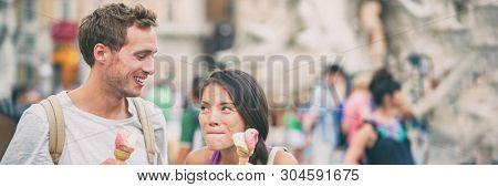 Summer fun funny girl eating ice cream licking lips goofy with man laughing. Young couple happy eating gelato cones on italy rome travel destination, Europe vacation banner panorama.