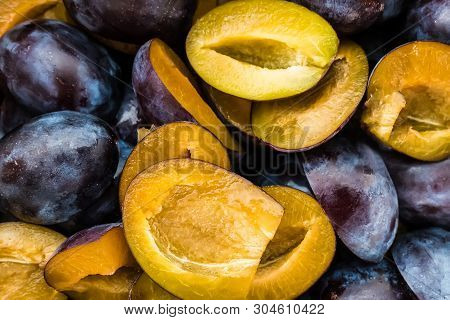 Fresh Sliced Plums. Blue And Violet Plums Background Texture.