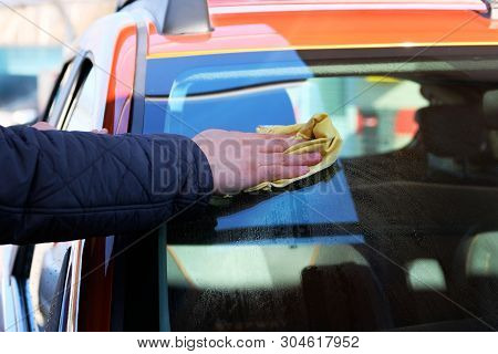 Man After Washing Wipes Windshield Of His Orange Car With A Yellow Rag At Car Wash. Close Up Of Male