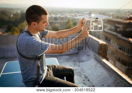 Young Technician Flying Uav Drone With Remote Control On Rooftop