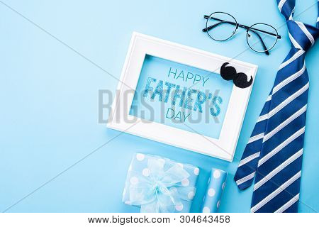Happy Fathers Day Concept. Top View Of Blue Tie, Beautiful Gift Box, White Picture Frame With Happy