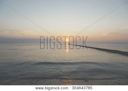 Sunset Over The Baltic Sea, Some Birds Are Sitting On A Groin