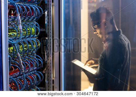 IT engineer testing new supercomputer while using digital tablet app, focus on open supercomputer cabinet with wires and cables