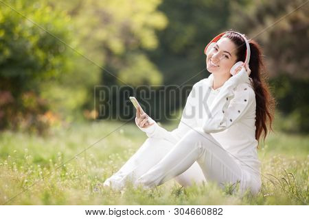 Happy woman with headphones relaxing in the park. Beauty nature scene with colorful background. Fashion woman enjoying the music from her mobile phone in summer season. Outdoor lifestyle