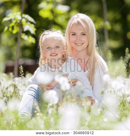 Happy mother and daughter relaxing in the park. Beauty nature scene with family outdoor lifestyle at spring or summer time. Happy stylish family resting together, having fun outdoor.