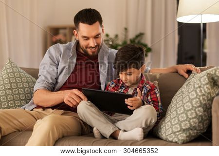 family, fatherhood, technology and people concept - happy father and little son with tablet pc computer sitting on sofa at home poster