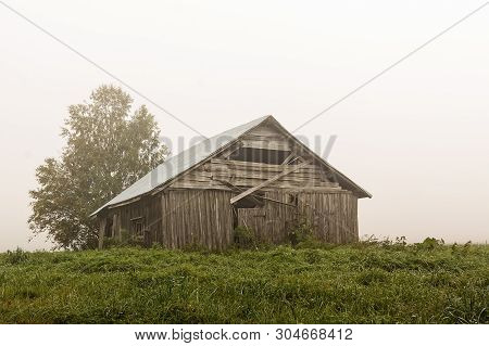 An Old Barn House Stands On The Summer Fields On A Very Foggy Morning At The Rural Finland. The Summ