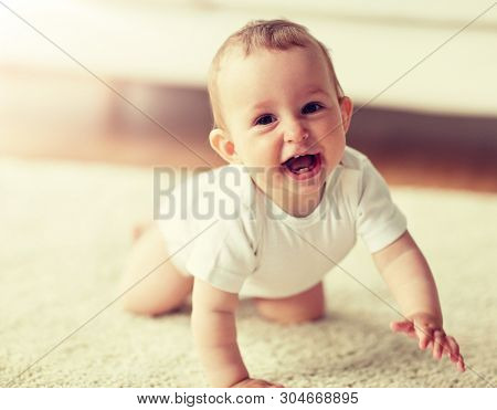 childhood, babyhood and people concept - happy smiling little baby boy or girl crawling on floor at home
