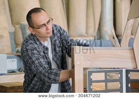 Male carpenter working in furniture joinery, master making wooden chair in wood workshop. poster