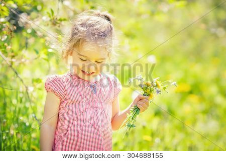 Happy little girl playing with bouquet in sunny park