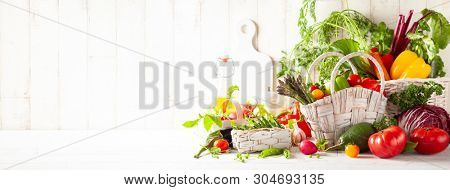 Still life with various types of fresh vegetables in baskets on a white wooden table. Concept of healthy eating, fresh vegetables.