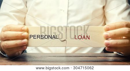 A Man Collects Wooden Puzzles With The Word Personal Loan. A Loan Issued By A Bank To Individuals Fo