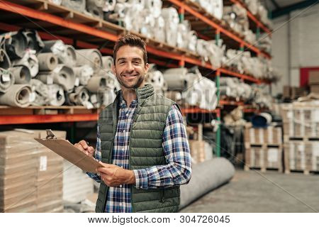 Smiling Worker Doing Inventory On A Warehouse Floor