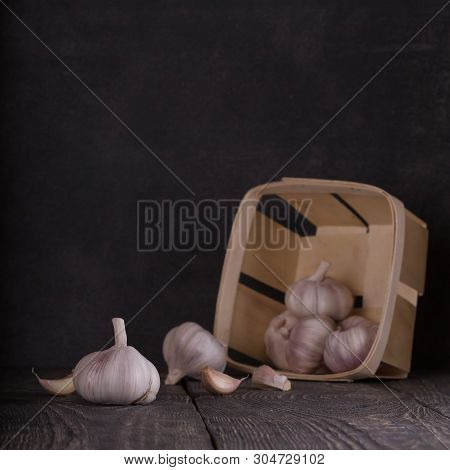 Scattered Heads Of Garlic On A Wooden Table, A Basket Of Garlic