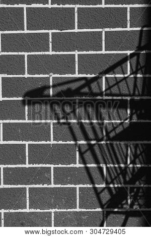 Idea Theft With The Shadow Of The Basket Trolley Black Brick Wall Background.