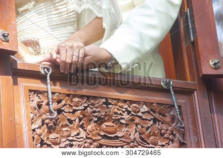 Thailand Tradition. Wedding Couple Holding Hands By The Window