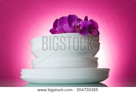 Clean Washed White Plates On A Pink Background And An Orchid Branch