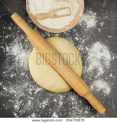 Top View. Delicate Yeast Dough For Pies, Rolling Pin And Flour On A Gray Background