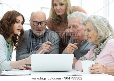 Two Senior Couples Talking With Consultant While Sitting At Table