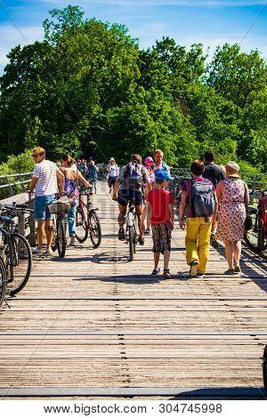 Munich,germany-june 2,2019: Crowds Walk Along Parked Bikes From  Beachgoers  On The Wooden Bridges B