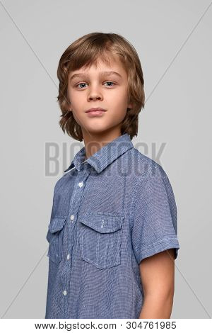 Confident youngster with blond hair wearing blue shirt and looking at camera while standing against gray background poster
