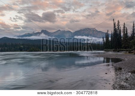 A Riverside View At Sunset Of The Athabasca River As It Weaves Its Way Through The Jasper National P