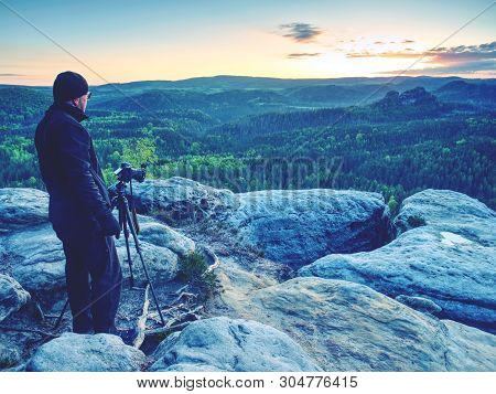 Photographer On A Mountain Cliff Taking Picture Of Landscape Awaking.   Dreamy Fogy Landscape Spring