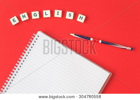 Word English On A Red Desk With A Pencil And A Blank Notebook And British English Union Jack Flag. F