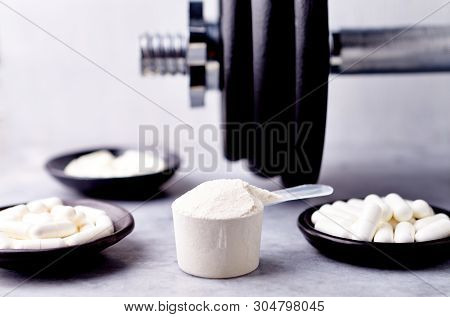 Scoop Of Whey Protein, Creatine, Taurine, Beta Alanine Capsules And A Dumbbell. Bodybuilding Food Su