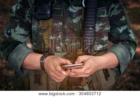 Mid Section Of Military Soldier Using Mobile Phone In Boot Camp War. Historical Re-enactment With A