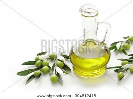 bottles of olive oil with olives on wooden background. Olive oil in bottle, leaves and olives