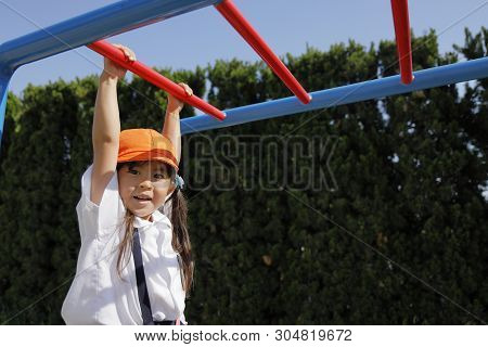 Japanese Girl In School Uniform Playing With A Monkey Bars (4 Years Old)
