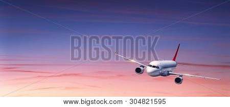 Passenger Airplane Is Flying In Colorful Sky At Sunset. Landscape With White Airplane, Purple Sky Wi
