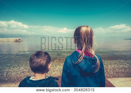 Little children standing on the shore and looking in admiration on Lake Ohrid, Republic of Macedonia poster