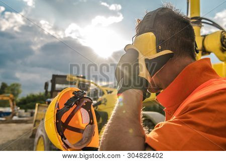 Construction Noise. Heavy Machinery Operator With Noise Reduction Headphones On His Head. Industrial