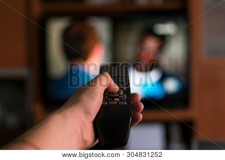 Hand Using A Remote To Change.