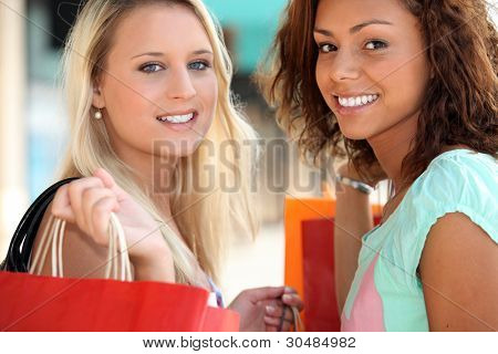 two 20 years old girls, a blonde and a metis doing shopping