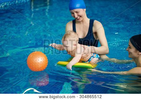Cute Active Little Child Playing In Swimming Pool. Baby Staying On Water With Board Helping And Tryi