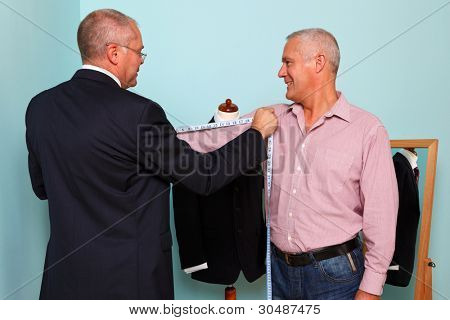 Photo of a tailor measuring a mans arm length during fitting for a new bespoke suit