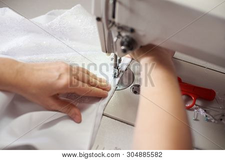 Clothier Woman Stitching White Dress On Sewing Machine At Workplace With Pins, Threads, Scissors On