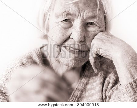 Sad elderly woman sitting at the table at home and looking miserably at only remaining coin from pension in her hand. poster
