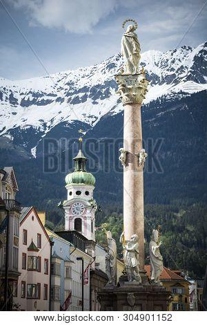 Column And Church With Alpine Backdrop In Innsbruck Austria
