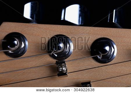 The Headstock Of An Electric Guitar On Black Background.