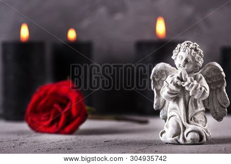 Mourning  Layout. Little Angel, Red Rose And Burning Candles On Grey Textured Background. Card For M