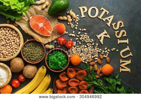 Food Rich In Potassium, Salmon, Legumes, Vegetables, Fruits, Nuts On A Dark Background. Healthy Food