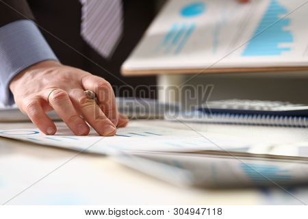 Person Controlling Prices Rise Accounting Income. Man Holding Pen Checking Financial Data On Chart.
