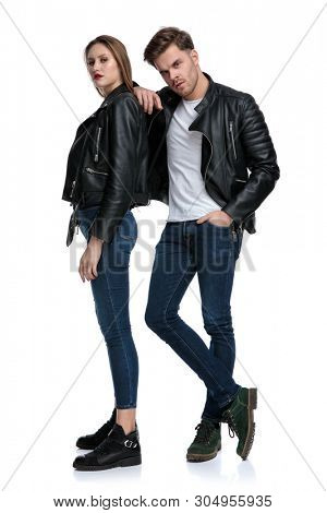 Determined punk couple posing and standing while he is leaning on her and holding his hand in his pocket, both wearing blue jeans and black leather jacket on white studio background