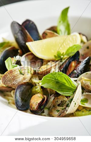 Exquisite Serving White Restaurant Plate of Spaghetti Nido with Sea Shells in Wine Sauce, Basil, Parsley and Celery. Homemade Italian Vongole Clams Linguini Pasta on Black Marble Table