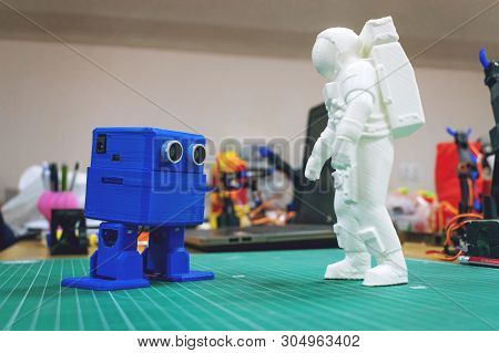 Kropivnitskiy, Ukraine - 12 May, 2018: 3d Printed Astronaut, Cosmonaut And Cute Robot On The Backgro