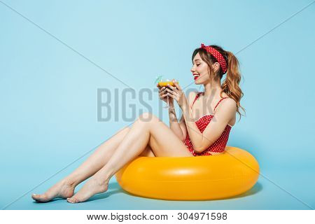 Beautiful young woman wearing swimsuit having fun at the beach with inflatable ring isolated over blue background, drinking cocktail